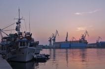 Fischerboote und Industrie am Hafen.