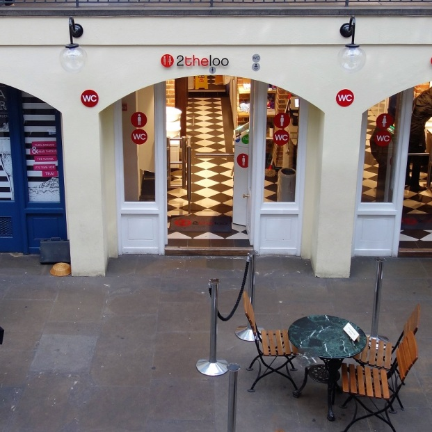 Links eine Opernsängerin, die Passanten mit ergreifenden Arien unterhält. Rechts das WC. Gesehen in Covent Garden.