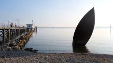 Bootsanlegestelle in Hagnau. Im Vordergrund eine Bootskulptur als Erinnerung an die Seegfrörne vor 55 Jahren. Damals war der Bodensee komplett zugefroren.